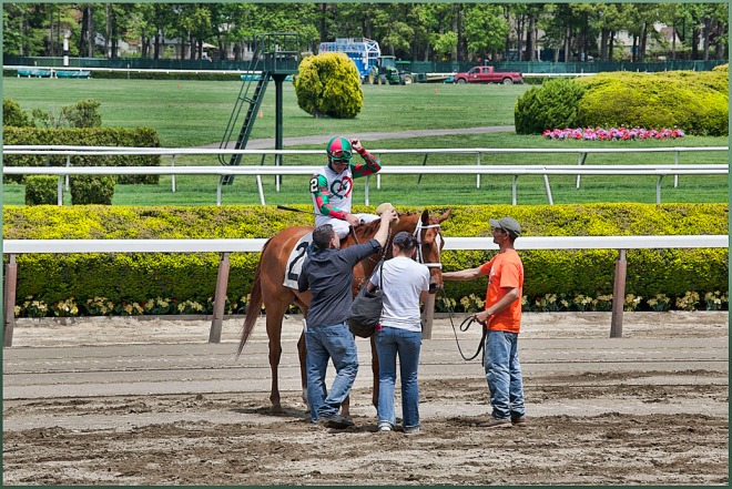 Stable hands wait for the winner of the 1st race, Tightened Touchdown with Jockey Joel Rosario on board...